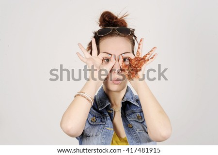 Funny attractive and trendy hipster girl clowning, happy lifestyle concept . Studio shot with grey background. - stock photo