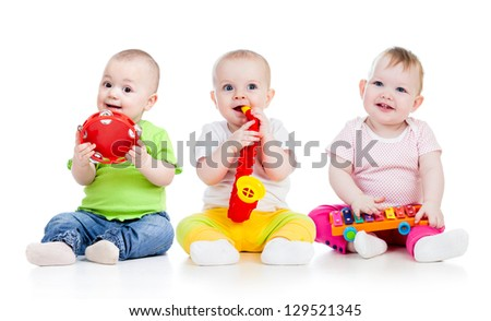 Funny babies girls  group with musical toys isolated - stock photo