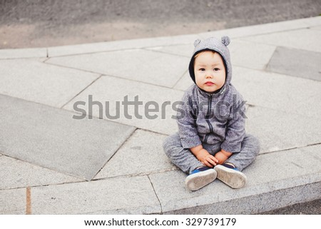 Funny baby boy in bear costume suit sits on a street pavement looking at camera. Gray pavement on background. Bear hood. Copy space. Baby fashion and loneliness concept. Mixed races multiethnic - stock photo