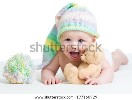 funny baby boy lying on bed with plush toy - stock photo