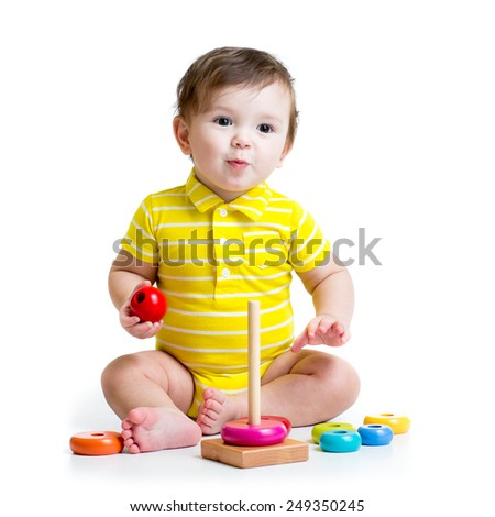 funny baby boy playing with colorful toy pyramid isolated - stock photo