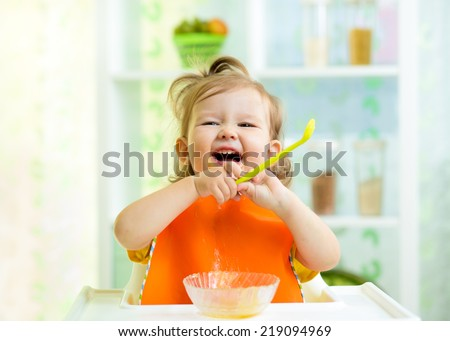 funny baby eating healthy food on kitchen - stock photo
