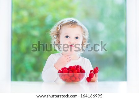 Funny baby girl eating raspberry at a white dining table next to a big window - stock photo