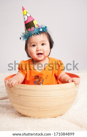 funny baby girl in basket on blanket - stock photo