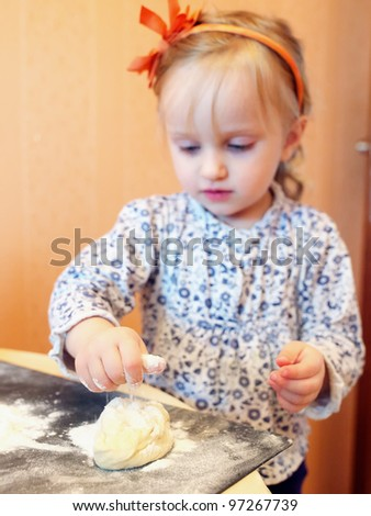 Funny baby girl knead the dough - stock photo