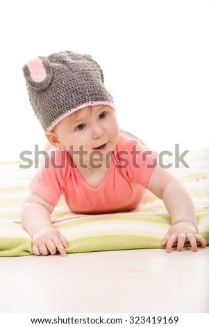 Funny baby girl laying down and wearing crochet bunny hat - stock photo