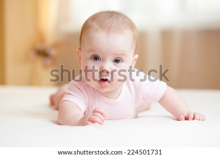 funny baby girl lying on white bed - stock photo