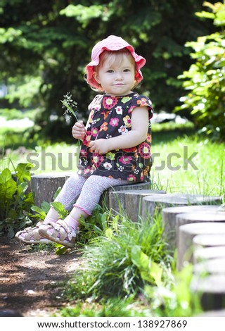 Funny baby girl on a little tree stump