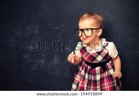 funny baby girl pupil in glasses and chalk at a school board  - stock photo