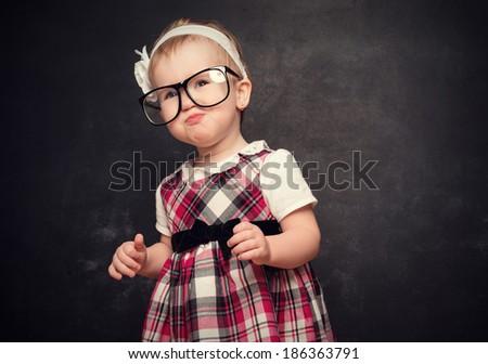 Funny baby girl pupil in glasses  at blackboard - stock photo