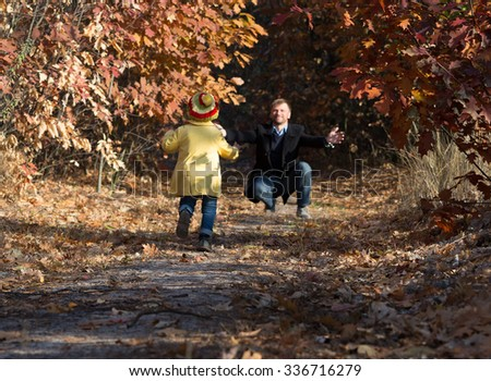 Funny Baby Girl Running towards Open Arms of Her Father along Alley in Autumnal Forest - stock photo