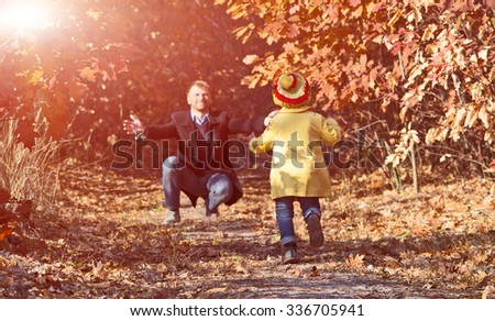 Funny Baby Girl Running towards Open Arms of Her Father along Alley in Autumnal Forest with Shine Shining Throw Golden Leaves - stock photo