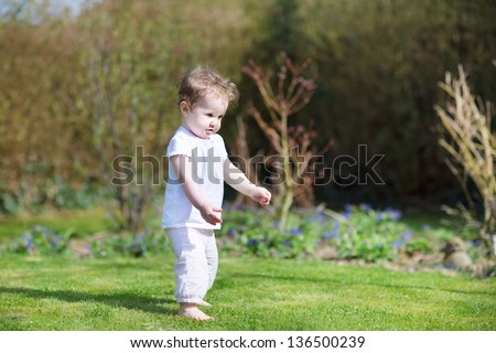 Funny baby girl taking her first steps in the garden - stock photo