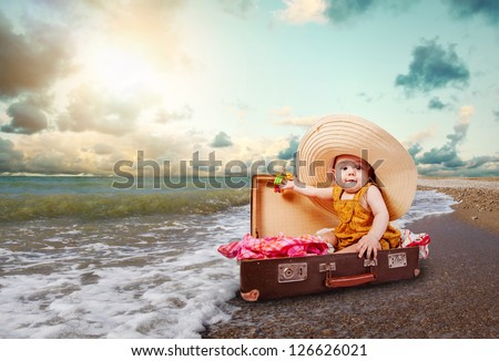 Funny baby girl traveler sitting in retro suitcase at the sea coast - stock photo