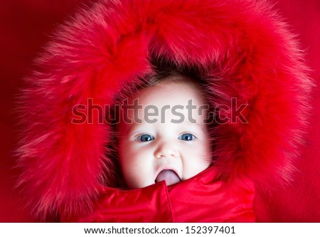 Funny baby girl with beautiful blue eyes in a warm winter jacket with a red hood - stock photo
