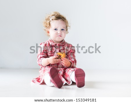 Funny baby girl with curly hair wearing a red dress eating a Christmas cookie in a white nursery - stock photo