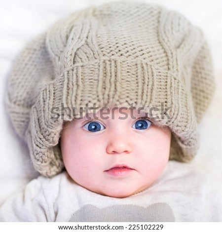 Funny baby in a big knitted hat - stock photo