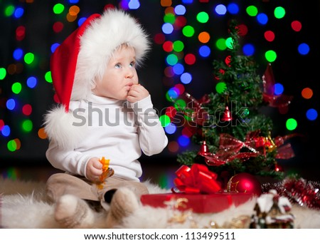 funny baby in Santa Claus hat on bright festive background - stock photo