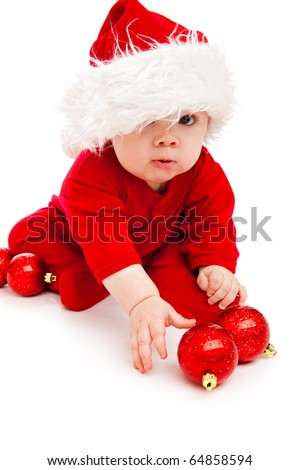 Funny baby in Santa hat and red bodysuit playing with Christmas balls - stock photo