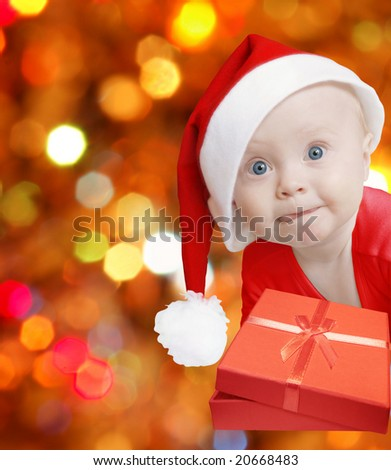 funny baby in Santa hat with present box on bright festive background, space for text - stock photo