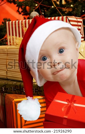 funny baby in Santa uniform, a lot of present boxes behind