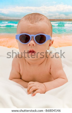 Funny baby in sunglasses on the beach - stock photo