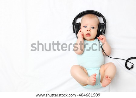 funny baby little boy in headphones - stock photo