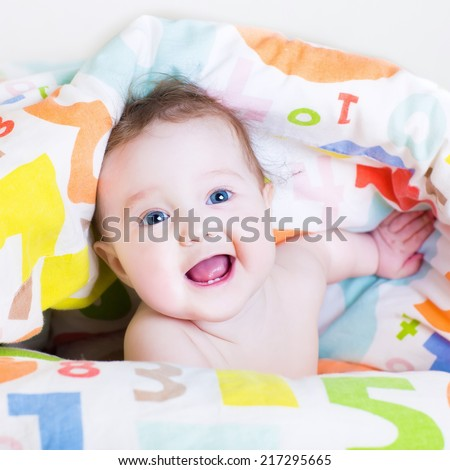 Funny baby playing peek-a-boo under a colorful blanket  - stock photo