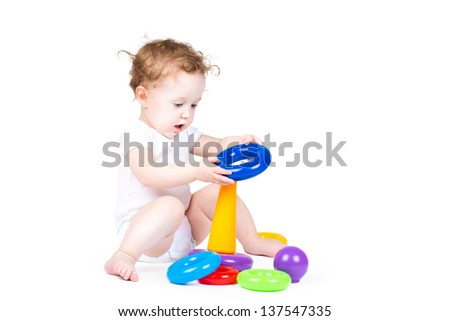 Funny baby playing with a colorful pyramid - stock photo