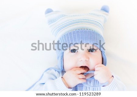 Funny baby playing with its hat - stock photo
