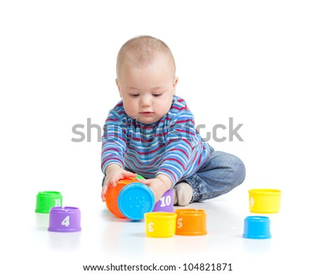 Funny baby playing with toys, isolated over white
