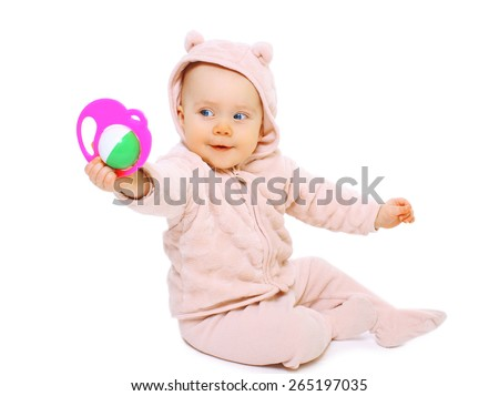 Funny baby sitting and playing with the rattle