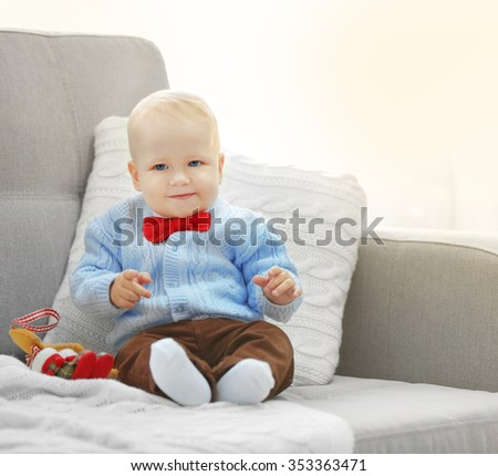 Funny baby sitting on sofa and Christmas tree on background