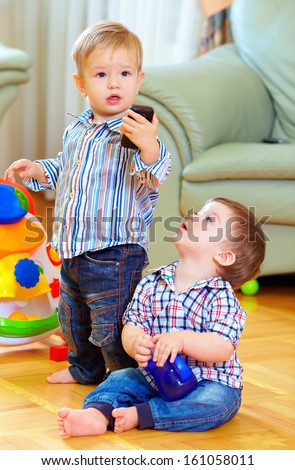 funny baby toddlers playing toys at home - stock photo