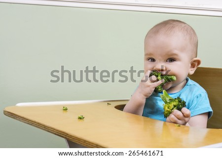 funny baby trying broccoli for the first time - stock photo