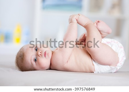 Funny baby weared diaper lying on bed - stock photo