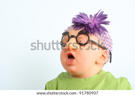 Funny baby wearing toy glasses and headband - stock photo