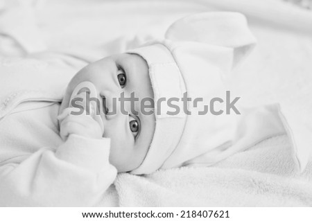 funny baby with dummy and ears hat - stock photo