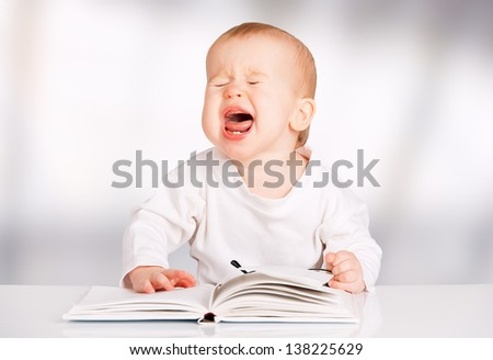 funny baby with glasses reading a book and cries - stock photo