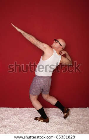 Funny bald Caucasian man shows off his biceps over maroon background - stock photo