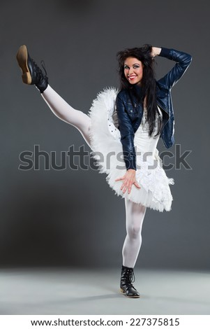 Funny ballet dancer. Female ballet dancer posing in boots and leather jacket. Full length studio shot on gray background. - stock photo