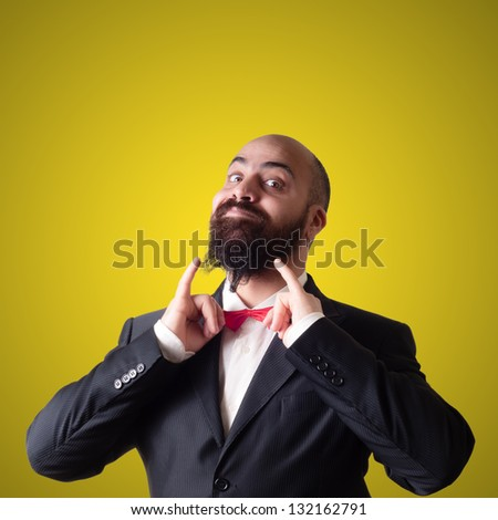 funny bearded elegant man with papillon on yellow background - stock photo