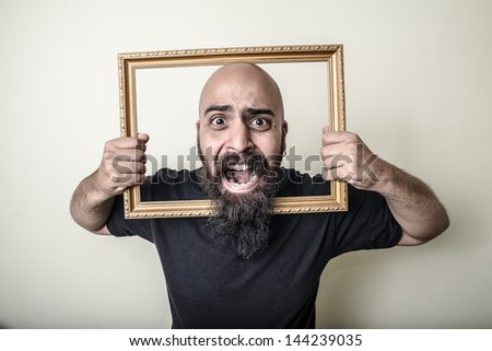 funny bearded man with golden frame on gray background - stock photo