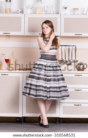 funny beautiful woman in the lush dress in kitchen