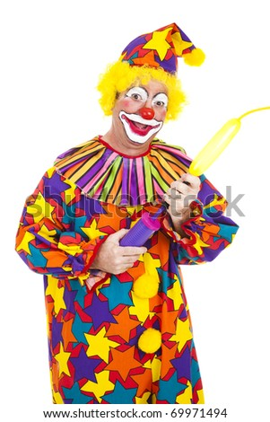Funny birthday clown blows up a balloon to twist into an animal shape.  Isolated. - stock photo