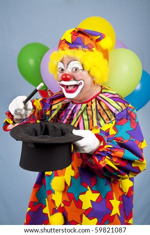Funny birthday clown does magic tricks with a top hat and wand. - stock photo