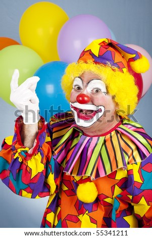 Funny birthday clown snapping his fingers.  Blue background with balloons. - stock photo