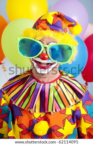 Funny birthday clown wearing over-sized novelty sunglasses. - stock photo