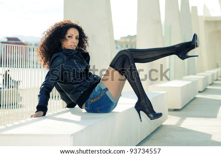 Funny black female model at fashion with high heels sitting on a bench - stock photo
