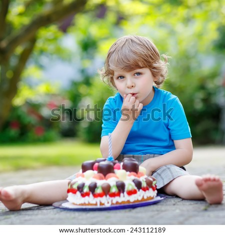 Funny blond boy celebrating his third birthday in home's garden with big cake. Happy child laughing about gifts and tasting cake. Outdoors on sunny day. - stock photo